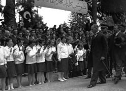 """Mustafa Kemal, Dolmabahçe'de kız öğrencilerle. Pankartta """"Hoş geldiniz Muhterem Gazi"""" yazıyor."""