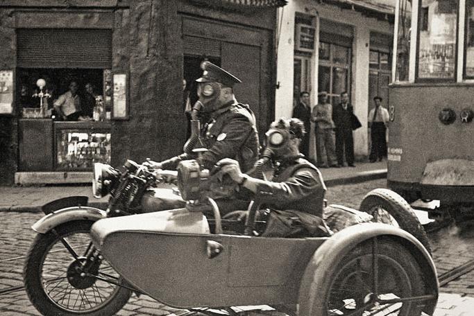 Namık Görgüç/Selahattin Giz: Two soldiers with gas masks in Beyoglu on a basketry motorcycle, Istanbul, 1939. Yapı Kredi Historical Archive