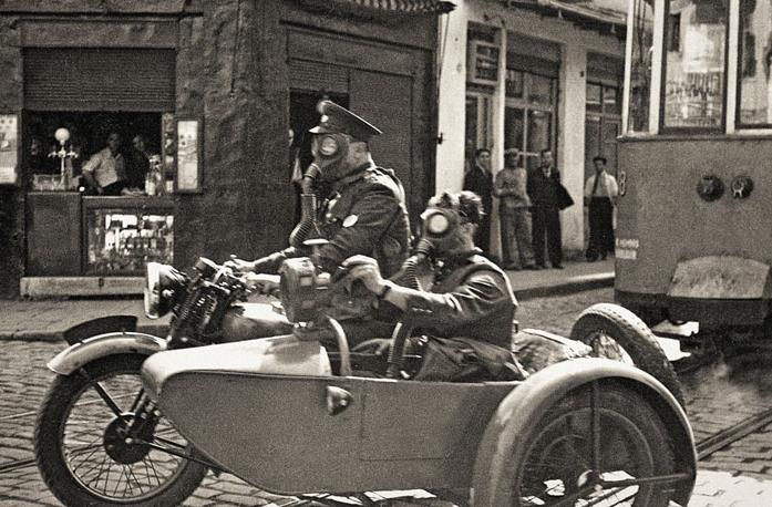 Namık Görgüç/Selahattin Giz: Gaz maskeli iki görevli Beyoğlu'nda sepetli motorsiklette, İstanbul, 1939. Yapı Kredi Tarih Arşivi