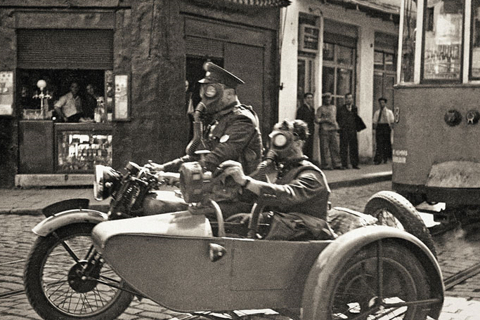 Namık Görgüç/Selahattin Giz: Two soldiers with gas masks in Beyoglu on a basketry motorcycle, Istanbul, 1939. Yapı Kredi Historical Archive